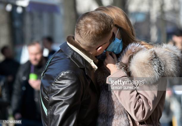 A man kisses a woman wearing a face mask amid concerns of the COVID19 coronavirus on a warm spring day in the Ukrainian capital of Kiev on March 19...