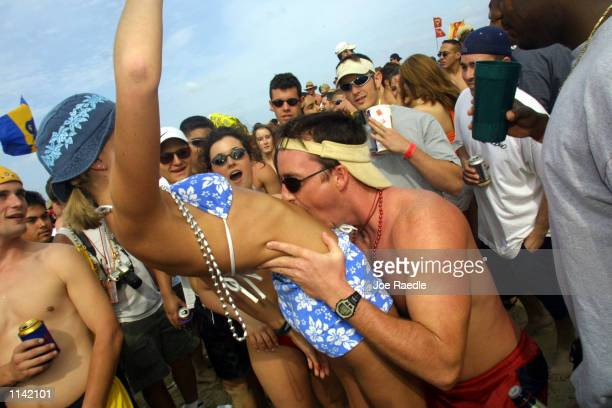 A man kisses a woman's stomach on the beach at South Padre Island Texas March 16 2001 during the annual rite of Spring Break Some 125000 revelers...