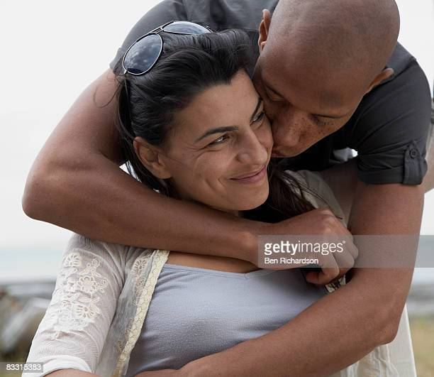 man kisses his female partner on the cheek - black women kissing white men stock pictures, royalty-free photos & images