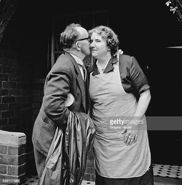 A man kisses his wife goodbye as he leaves for work in a Welsh mining town probably in Monmouthshire in southeastern Wales 1955