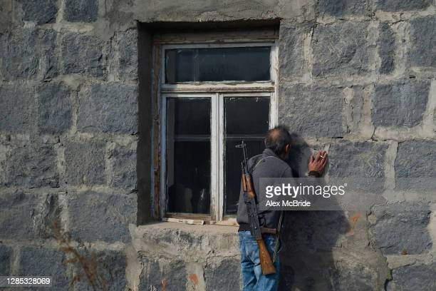 Man kisses the walls of his home before abandoning it as fear of Azeri persecution prompts him to leave his homeland on November 12, 2020 in...