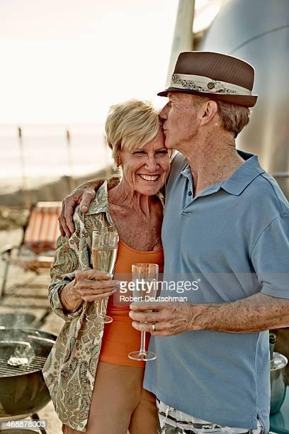 A man kissing a woman's forehead.