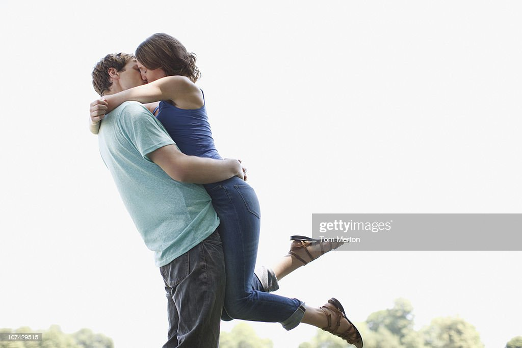 Man kissing and lifting wife outdoors : Stock Photo