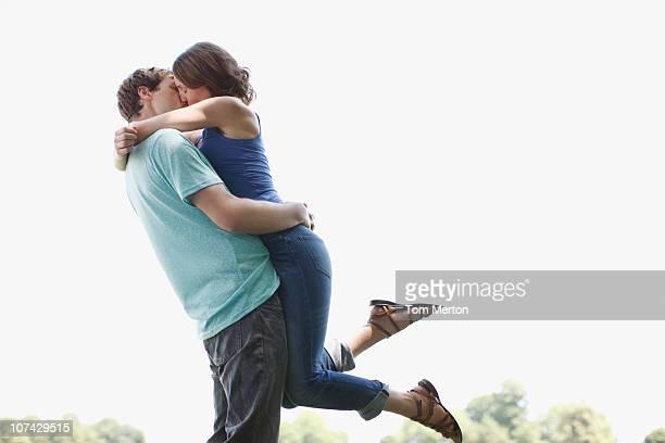 Hombre Besando a la mujer al aire libre y levantar