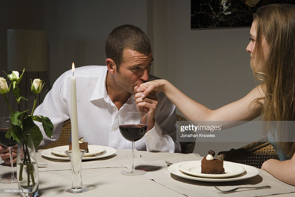 Man kissing back of woman's hand at candlelit dinner : Stock Photo