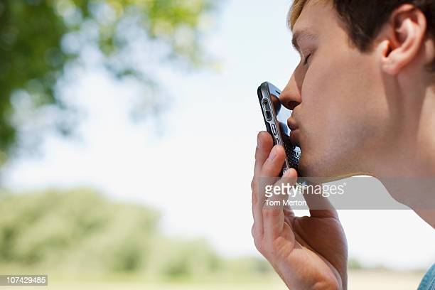 Man kissing cell phone outdoors