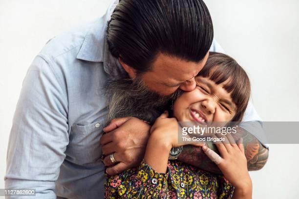 Man kissing daughter on cheek