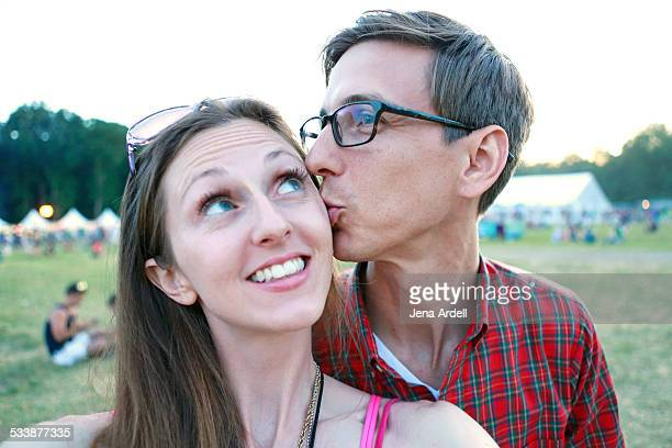 Man Kissing Girlfriend at Outdoor Music Festival