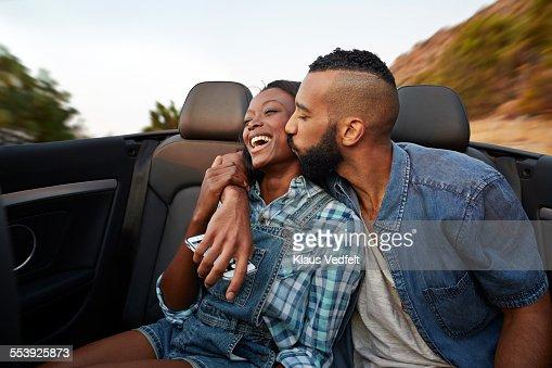 Man kissing girlfriend in the backseat of car