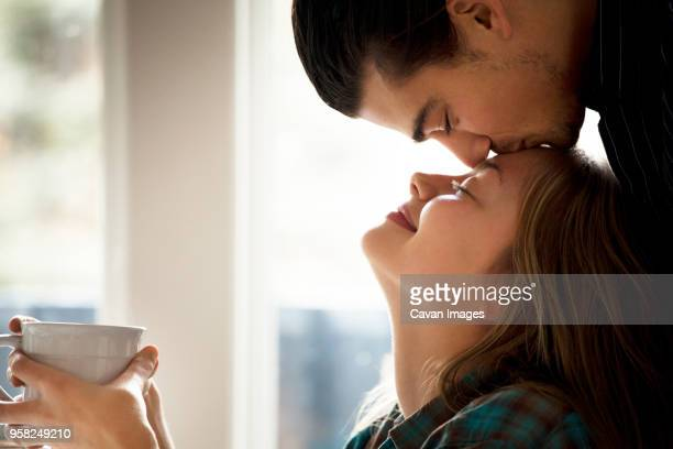 man kissing girlfriend on forehead at home - キス ストックフォトと画像