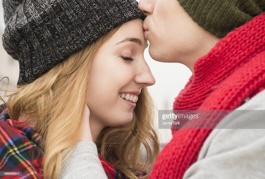 Man kissing girlfriend on head