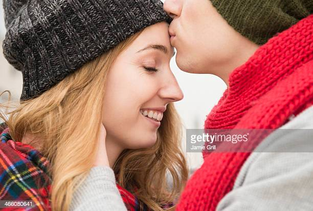 man kissing girlfriend on head - vriendje stockfoto's en -beelden