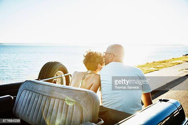 Man kissing girlfriend sitting in convertible