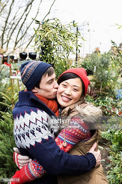 Man kissing girlfriend while holding mistletoe..