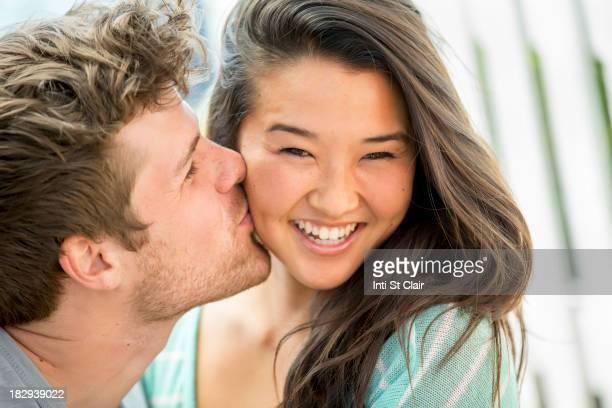 Man kissing girlfriend's cheek outdoors