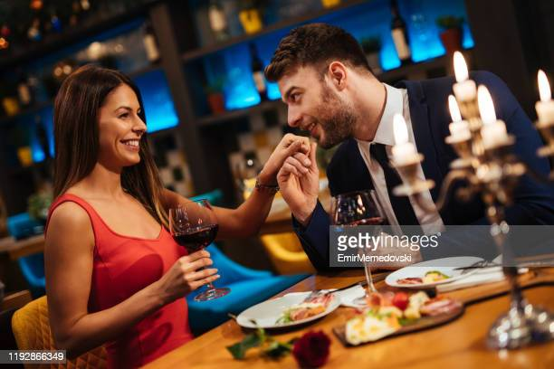 man kissing his girlfriend's hand during romantic dinner - valentines day dinner stock pictures, royalty-free photos & images