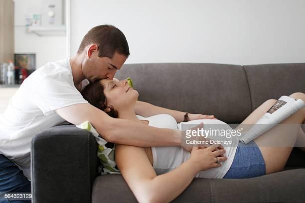 a man kissing his pregnant woman - mari photos et images de collection