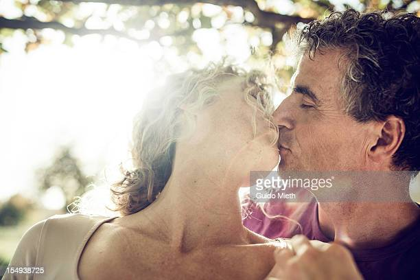 Man kissing his wife under a big tree.