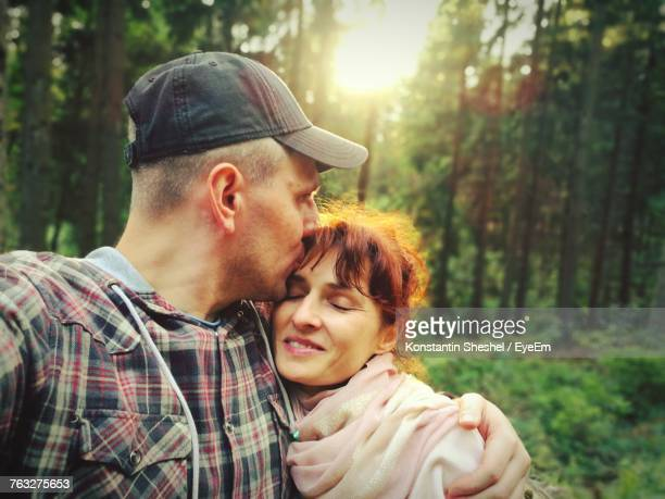 Man Kissing On Girlfriends Forehead While Standing In Forest