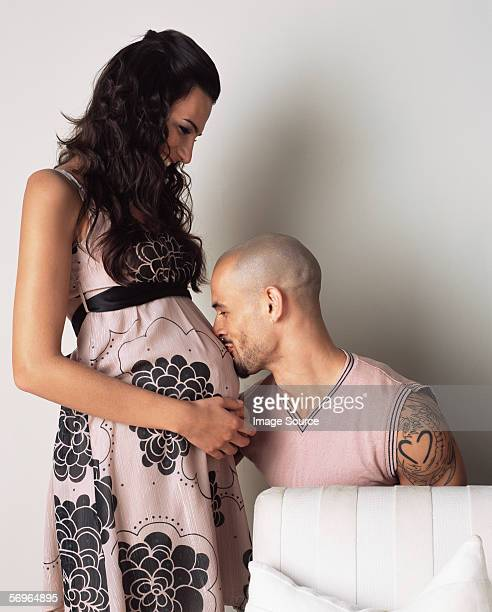 Man kissing pregnant woman's belly
