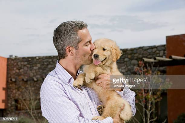 man kissing puppy - alleen één mid volwassen man stockfoto's en -beelden