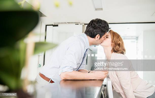 man kissing receptionist - work romance stock pictures, royalty-free photos & images