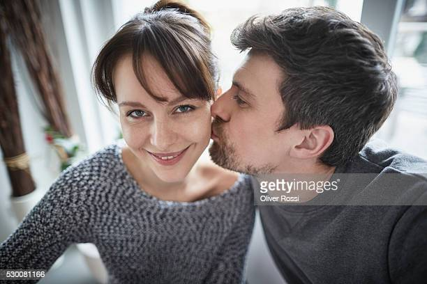 man kissing smiling woman's cheek - cheek stock pictures, royalty-free photos & images