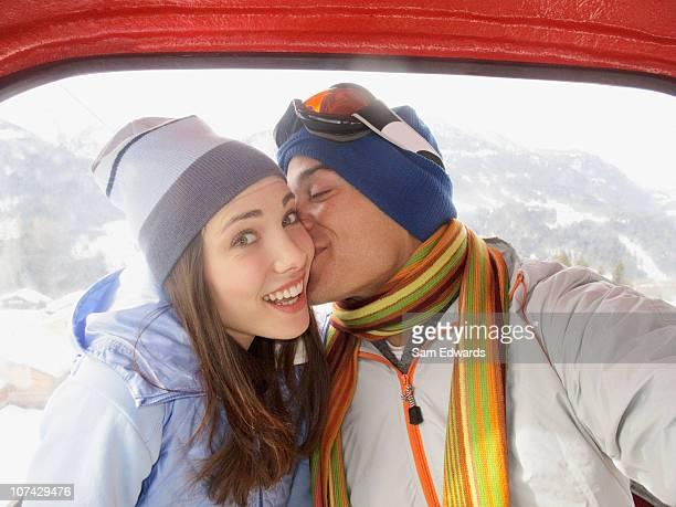 Man kissing wife in ski lift