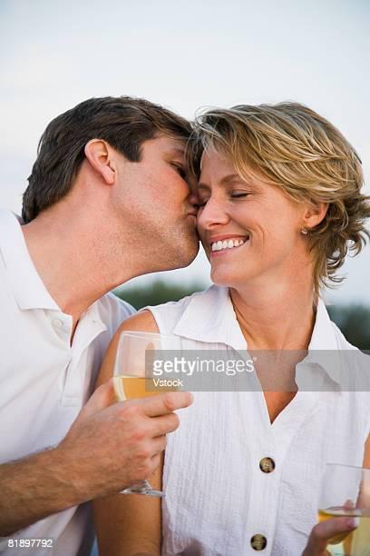 Man kissing wife?s cheek