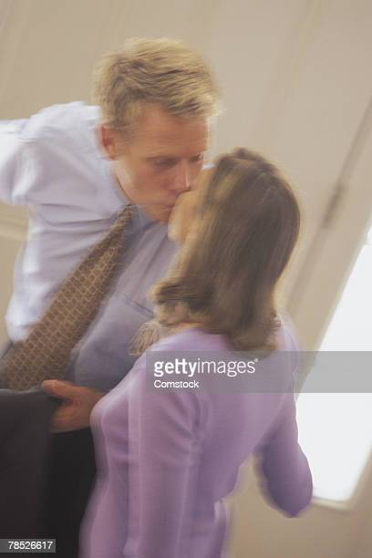 Man kissing woman before leaving
