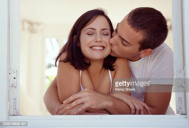 man kissing woman by window - cheek stock pictures, royalty-free photos & images