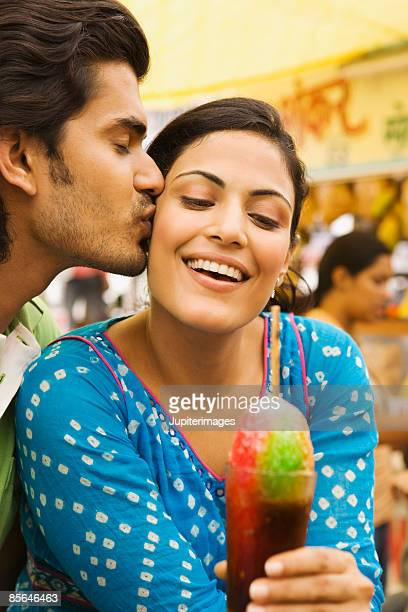 Man kissing woman holding baraf gola
