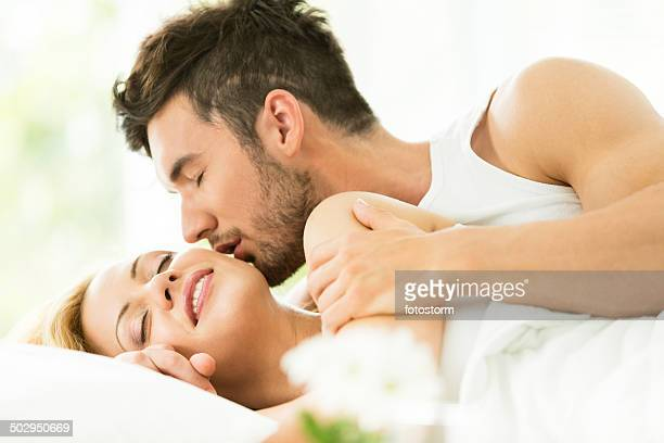 man kissing woman in bed - kissing stock pictures, royalty-free photos & images