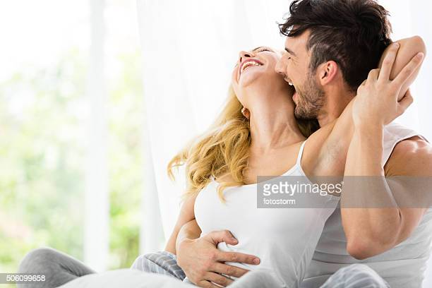 man kissing woman in bed - erotische stockfoto's en -beelden