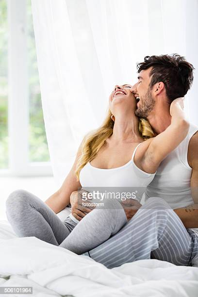 Man kissing woman in bed