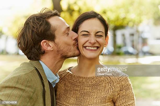 man kissing woman in park - uomini di età media foto e immagini stock