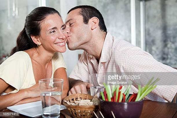 Man kissing woman on cheek at table