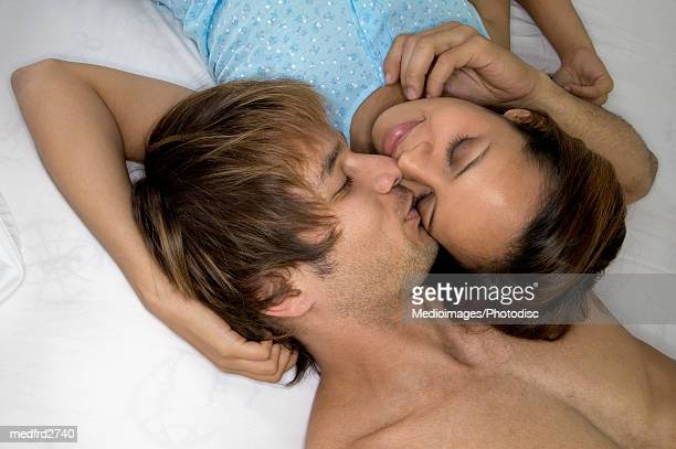Man kissing woman on cheek in bed, close-up