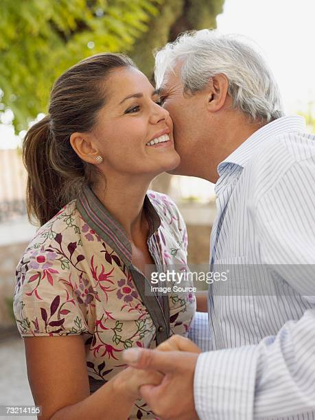 man kissing woman on cheek - sugar daddy stock photos and pictures