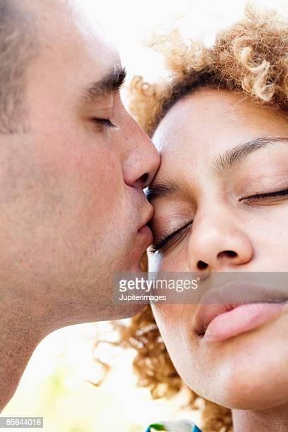 Man kissing woman on eyelid