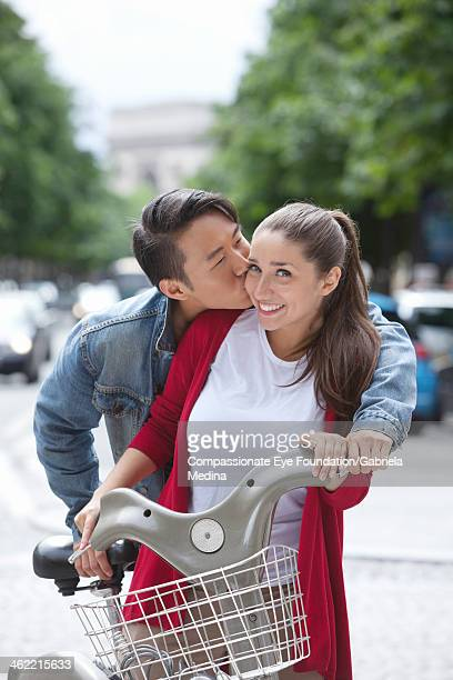 "man kissing woman with scooter on city street - ""compassionate eye"" stock-fotos und bilder"