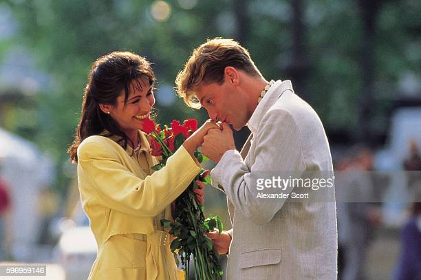 Man kissing woman's hand as she holds bouquet of roses