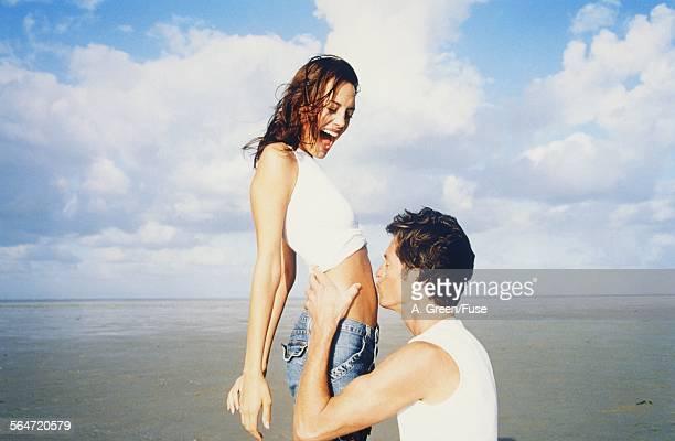 Man Kissing Womans Midriff on Beach