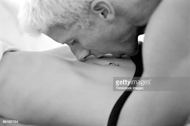 Man kissing woman's stomach