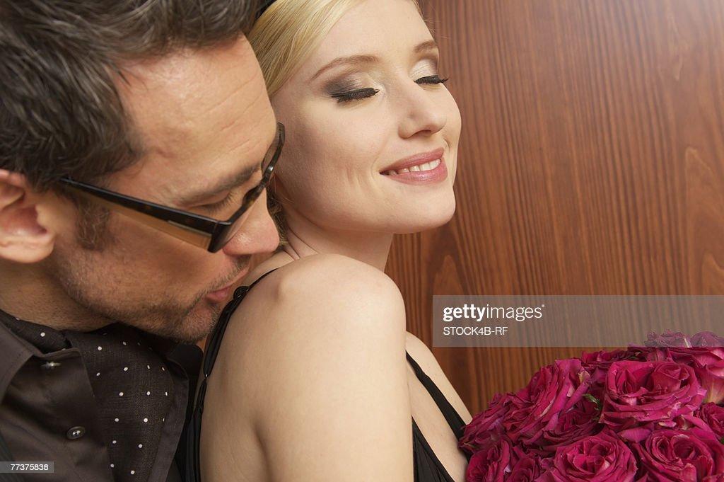 Man kissing young woman's shoulder : Photo