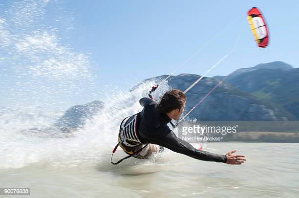 man kiteboarding, on water