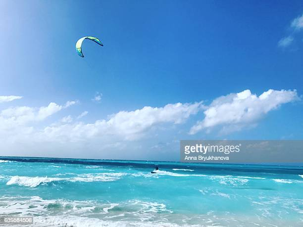 man kitesurfing on grace bay beach. turks and caicos islands - grand bahama stock photos and pictures