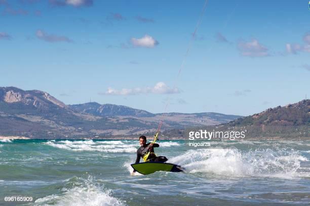 man kitesurfing with strapless surfboard, los lances beach, tarifa, cadiz, andalucia, spain - tarifa stock pictures, royalty-free photos & images