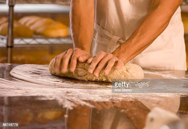 Man kneading dough at bakery