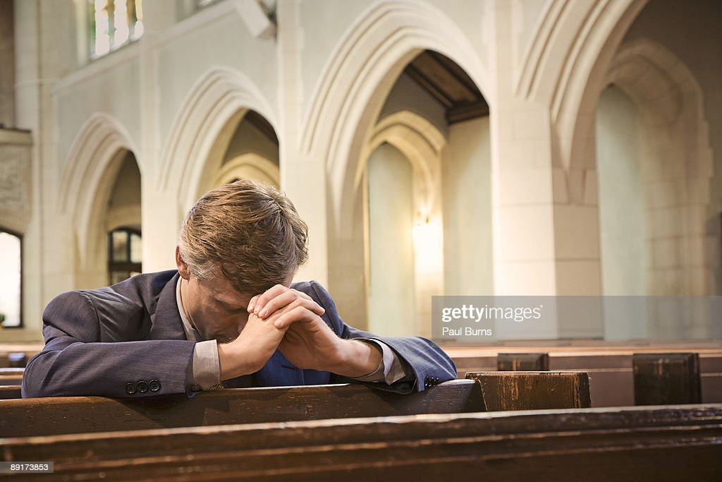 Man Kneeling and Praying in Church : Stock Photo